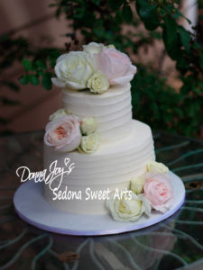 ribbed tuscan wedding cake adorned with fresh flowers